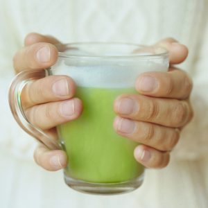 Female hands holding cup of green matcha tea closeup